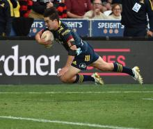 Highlanders winger Connor Garden-Bachop, on debut, lunges to score a try during their opening...