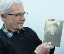 Bob Britton holds a portrait of his father, Bill, who rescued Prince Philip from Corfu in 1922....