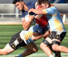 University defenders hooker Ricky Jackson (left) and No 8 Luke Russell stop Harbour loose forward...