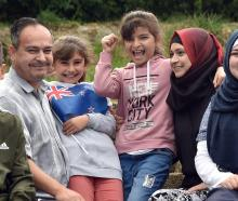 Showing off their new flag are the Haroura family, (from left) Ousama (14), Mohamad, Lina (8),...