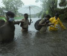 Frontline workers help people cross a flooded street after heavy rainfall caused by Cyclone...