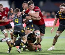 Crusaders captain Scott Barrett is tackled by Chiefs captain Brad Weber during Saturday's Super...