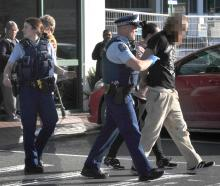 The alleged offender is led away by police after being apprehended in the supermarket. Photo:...
