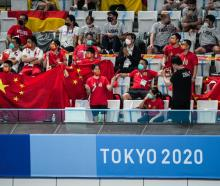 Members of the Chinese delegation support athletes during the Men's 10 metre Synchronized...