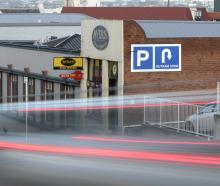 Traffic streams past a new inner city Dunedin sign which cheekily suggests that the only parking...