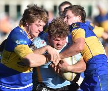 University No 8 Luke Russell tries to force his way past Taieri's Nick Henderson (left) and...