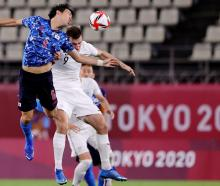 Japan's Wataru Endo and  Olywhite Chris Wood compete for the bal. Photo: Reuters