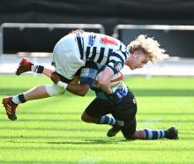 Otago Boys' High School winger Aaron Morrison is tackled by Nelson College opposite Timoci Sauvia...