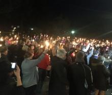Hundreds attend a vigil led by Timaru Hospital chaplain Alan Cummins (below) for three girls...
