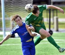 Green Island player Cam Brewitt gets to the ball before his Mosgiel opponent Rhys Quarrell in a...