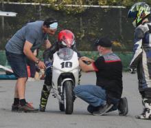 Bede Cordes (left) steadies the Kayo MiniGP bike, Motorcycling Canterbury rider trainer Shannon...