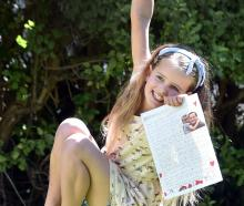 Amelie Harrop, of Dunedin, displays the letter she wrote to the Prime Minister asking for her...