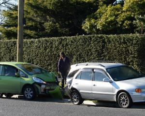 A woman, inspects the aftermath of a two-car crash in Dunedin. Photo by Linda Robertson.