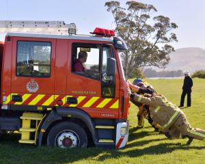 Firefighters try to free the Palmerston volunteer brigade fire engine after it became stuck while attending an accident at Karitane in which a car ended up down a bank yesterday morning. Photos by Gerard O'Brien.