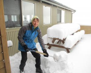 Author Alina Suchanski shovelling snow off the Luxmore Hut decking as part of her hut warden...