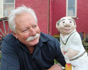Antique store-owner John McCartan with his 20-year-old cricket garden figurines which he has set...