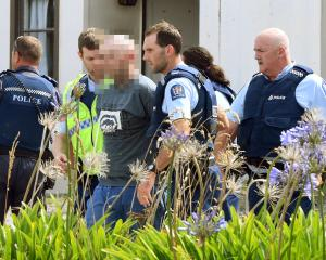 A man is led away from a Taieri Mouth house by police following a machete attack. Photos: Stephen...