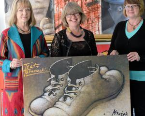 Polish Heritage of Otago and Southland Charitable Trust members (from left) Ewa Rozecka-Pollard, Cecylia Klobukowska and Bozena Misiewicz-Haug holding a poster by Mieczyslaw Gorowski of 1989. Photos by Linda Robertson.