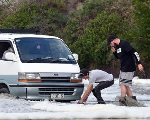 Rescuers attach a strop to a van stranded in sand as the tide rises at Tomahawk Beach yesterday. Photos: Peter McIntosh.