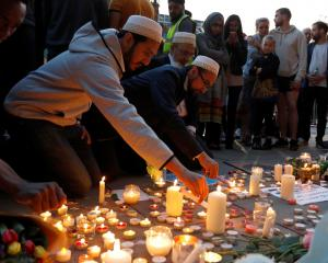 Men light candles following a vigil in central Manchester. Below: Candles and messages of condolence are left for the victims. Photos: Reuters