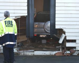 A firefighter inspects a Honda CR-V driven through a wall of the gymnasium at Arai Te Uru Whare...