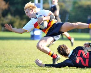 Waitaki Boys' High School replacement Bayley Sullivan ankle-taps John McGlashan College back Andrew McKenzie during an Otago premier schools game at McGlashan on Saturday. Photo: Christine O'Connor.