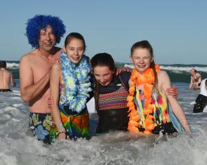 Polar plungers (from left) Mike McConachie, Tessa McConachie (14), Emma Andrews (13) and Annabelle Bilkie (14), all of Dunedin, are all smiles despite the chilling water of St Clair Beach at the 88th Polar Plunge yesterday. Photos: Gregor Richardson