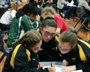 Bluestone School's Lucy Park (12, left), Paris Williams (12) and Zoe Ryan-Thomson (12) put their spelling skills to the test in the Year 7-8 quiz late last night. Photo: Alexia Johnston