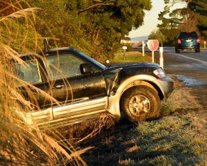 A SUV in a ditch beside slippery State Highway 1 in East Taieri yesterday. Photos: Stephen Jaquiery.