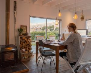 Emma-Kate Moore (33) works at her kitchen table inspired by the views of Kingston from her...