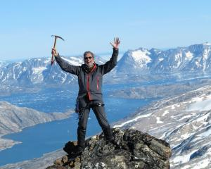 Mountaineer David Woods reaches the peak of a never-before-climbed mountain in Greenland in 2013....