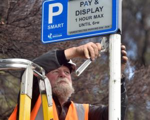 Michael Bennett of Downer puts up the new DCC smart-parking sign outside First Church in Moray Pl...