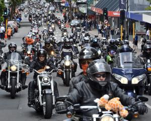 Bikers rumble down George St yesterday to collect Christmas gifts for children in need. Photos:...