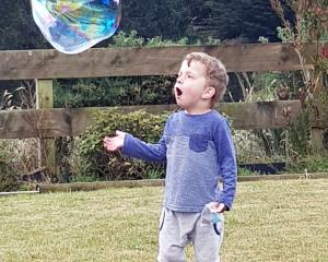 Riley Moore is excited to play with bubbles blown by his aunt on Christmas Day at Taieri Mouth....
