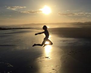 Isabel Martin (8), of Wanaka, jumps for joy at the start of the school holidays as the sun sets...
