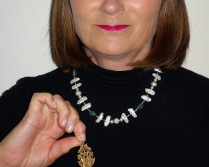 Sandra Robinson with a gold fob her father found in the mud of the Mataura River, which she is...