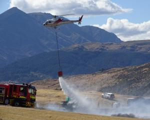 A helicopter drops water on a fire in The Preserve residential area at Jacks Point yesterday afternoon. Photo: Alister Brown
