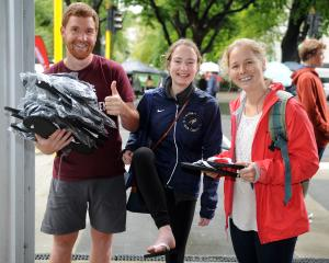 Student Life member Cam Mackenzie (left) distributes jandals to students Claire Connors and...