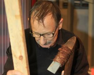 New Zealand's foremost expert stone tool-maker, Dante Bonica, of Auckland, demonstrates how a stone tool he  made would be used, at the North Otago Museum in Oamaru this week. Photos: Hamish MacLean