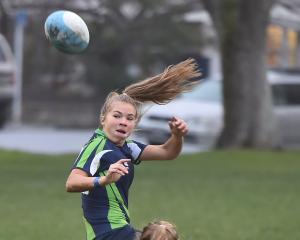 Tash Iti (16) of Otago Girls' High School, charges the ball up while Te Aroha Little (17) of South Otago High School attempts to slow her down. Photos: Gregor Richardson