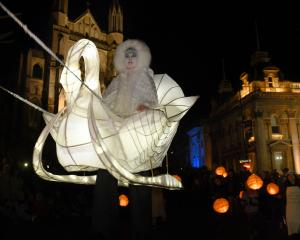 Stilt walker Mary Cocker, of Dunedin, appears to be floating in midair in a swan-themed carriage...