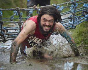 Mud, Sweat and Tears men's 10km winner Jonah Smith, of Dunedin, crawls through a muddy ditch....