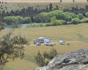 Crash investigator and police vehicles are parked near the scene of a Wanaka helicopter crash...