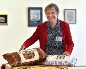 "Otago Embroiderers' Guild member Barbara Smith with two cushions, by Aggie O'Leary (at left) and Julie Dawkins, at the guild's ""In Stitches'' 2018 exhibition. Photos: Peter McIntosh"