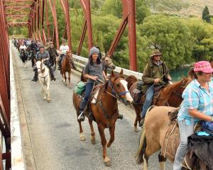 Riders on Bill Butler's cavalcade trail cross the Clyde bridge, much to the delight of onlookers...