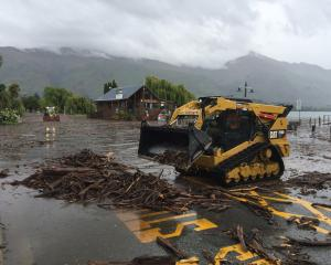 Heavy machinery clears debris from the Wanaka lakefront this afternoon. Photo: Gregor Richardson