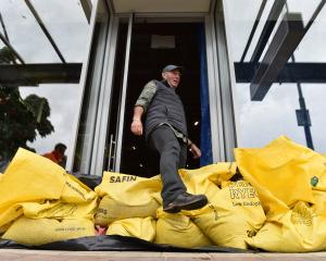 Mark Sanders from the sports shop Southern Wild in Wanaka steps over his sandbagged front door to...