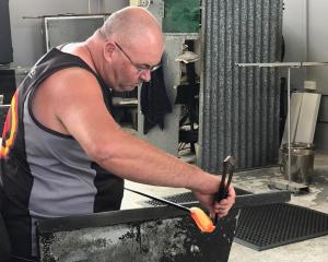 A glassblower creating a little blue penguin at Hokitika Glass Studio.
