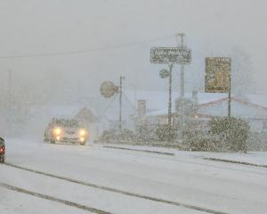 Traffic crawls through blizzard-like conditions in Waihola.