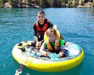 Bryn (21) and Fletcher (8) Hill enjoy some biscuiting on a calm, sunny day on Lake Benmore, on...